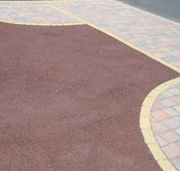 Advantages & Disadvantages of tarmacadam - Red tarmacadam driveway with block paved border